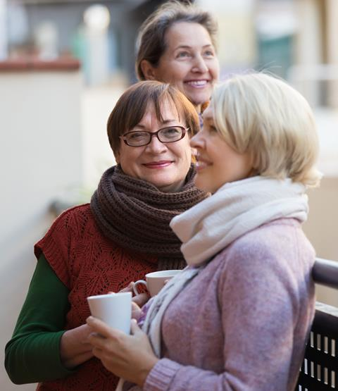 Mature group of female friends smiling and drinking tea on a balcony